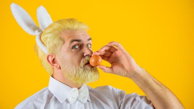 Mężczyzna z uszami królika całuje jajko wielkanocne, polowanie na jajka, człowiek-króliczek, ferie wiosenne.