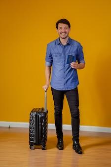 Mężczyzna z walizką i paszportem na żółtym tle. koncepcja podróży
