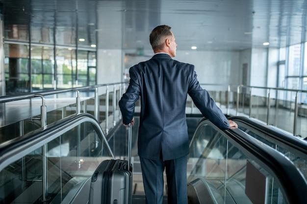 Mężczyzna z walizką na schodach ruchomych tyłem do aparatu