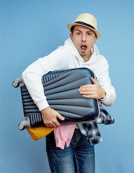 Mężczyzna z walizką spieszy do samolotu, rzeczy wypadają z bagażu