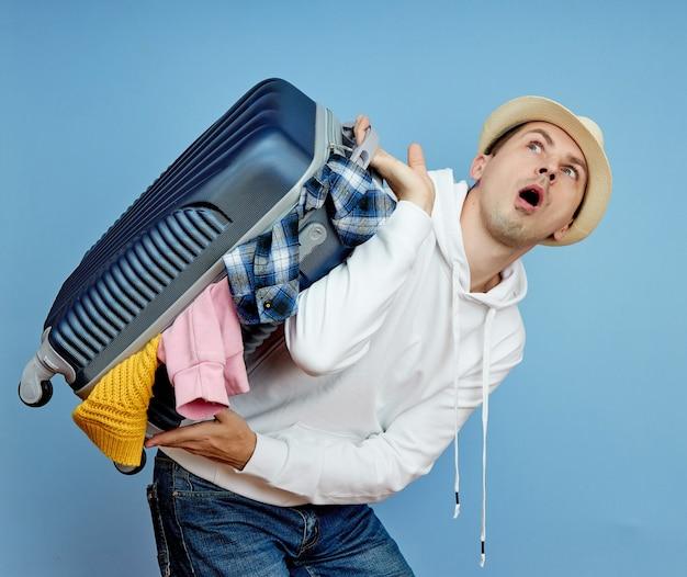 Mężczyzna z walizką spieszy się do samolotu, rzeczy wypadają z bagażu