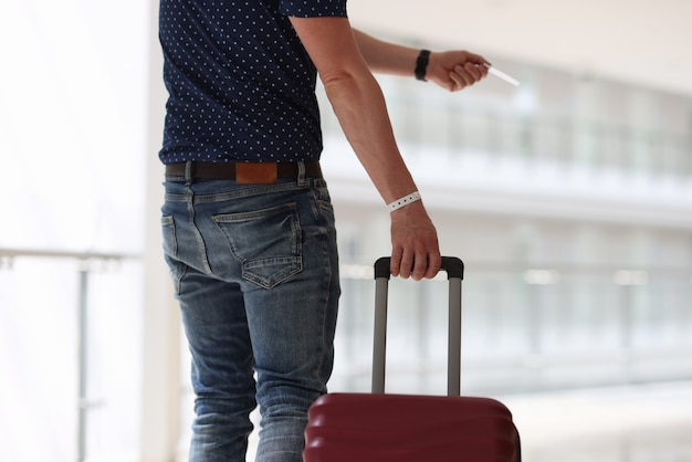 Mężczyzna z walizką trzymający plastikowy klucz do zbliżenia pokoju hotelowego