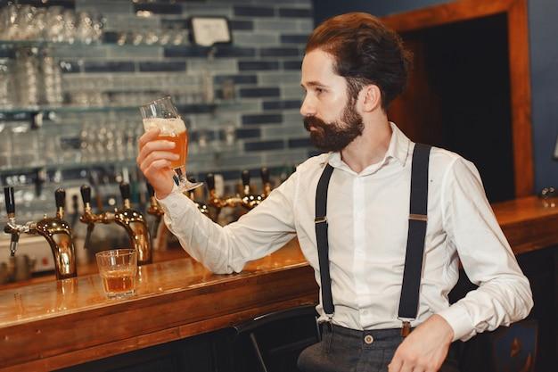 Mężczyzna z wąsami i brodą stoi przy barze i pije alkohol ze szklanki.