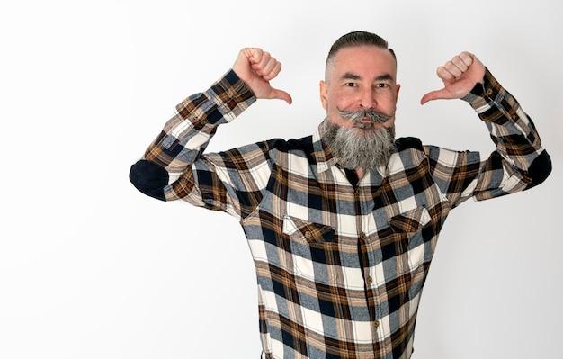 Mężczyzna z wielką brodą i wąsami w koszuli w kratę unoszący ręce i wskazujący na siebie śmieszną miną i bezpośrednim spojrzeniem