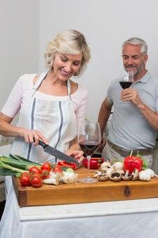 Mężczyzna z wina szkłem i kobiety sieka warzywa w kuchni