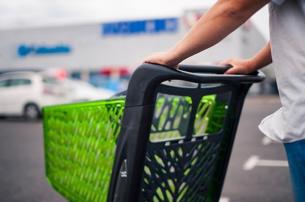 Mężczyzna z wózkiem supermarketu na parkingu