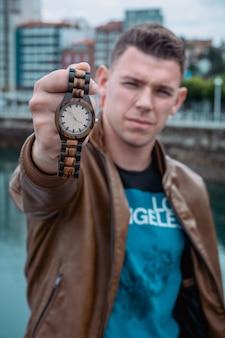 Mężczyzna z wyciągniętym ramieniem pokazuje zegarek