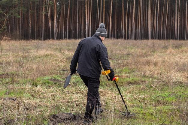 Mężczyzna z wykrywaczem metalu idący przez pole z drzewami w tle