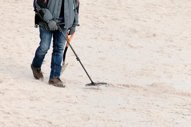 Mężczyzna z wykrywaczem metalu szuka klejnotów.