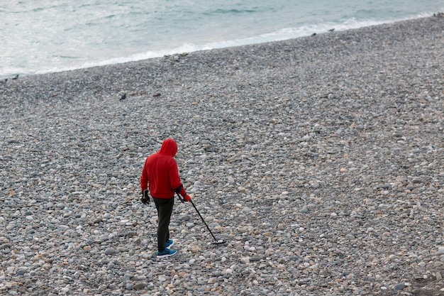 Mężczyzna z wykrywaczem metalu szuka monet i biżuterii na plaży