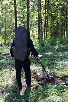 Mężczyzna z wykrywaczem metalu w lesie w poszukiwaniu zabytkowych przedmiotów i cennych monet