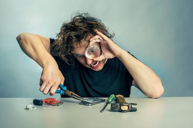 Mężczyzna z wyrazem paniki na twarzy, naprawiający telefon