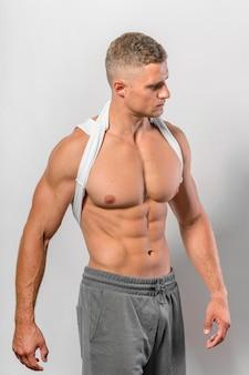 Mężczyzna z wysportowanym ciałem pozuje, zakładając podkoszulek na szyję
