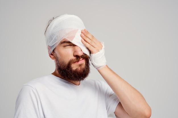 Mężczyzna z zabandażowaną głową i izolowanym tłem krwi w oku