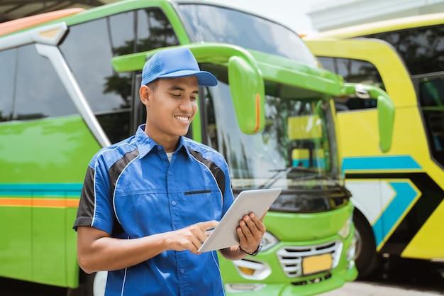 Mężczyzna z załogi autobusu w mundurze i kapeluszu uśmiecha się, używając cyfrowego tabletu na tle floty autobusów