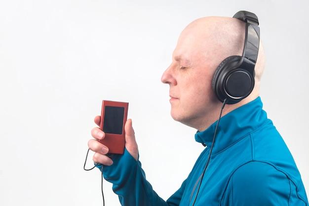 Mężczyzna z zamkniętymi oczami słucha muzyki przez słuchawki