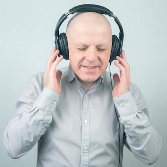 Mężczyzna z zamkniętymi oczami słucha muzyki w słuchawkach na jasnym tle