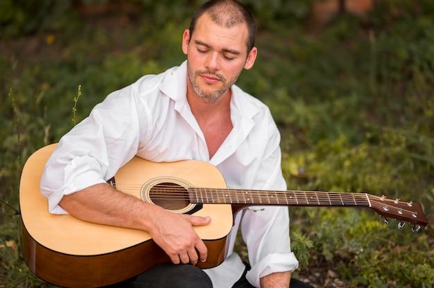 Mężczyzna z zamkniętymi oczami trzyma gitarę