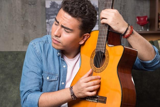 Mężczyzna z zamkniętymi oczami trzyma piękną gitarę i siedzi na kanapie. wysokiej jakości zdjęcie