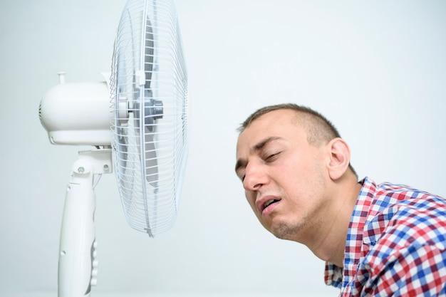 Mężczyzna z zarostem na twarzy cierpi z powodu upału i próbuje ochłodzić się przy wentylatorze.