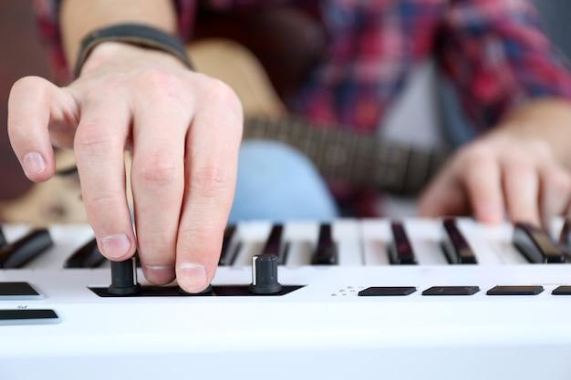 Mężczyzna z zbliżeniem gitary i syntezatora