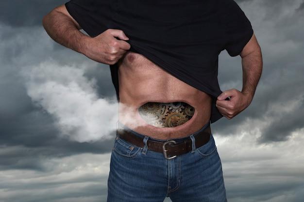 Mężczyzna z zębatkami dymiącymi w brzuchu