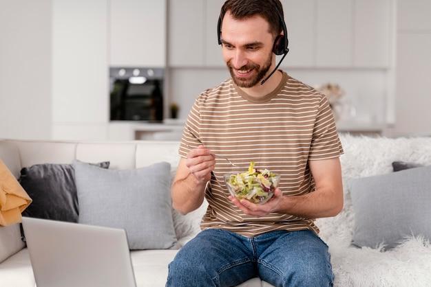 Mężczyzna z zestawem słuchawkowym je podczas rozmowy wideo