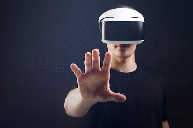 Mężczyzna z zestawem słuchawkowym vr dotyka niewidzialnego obiektu