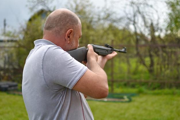 Mężczyzna z zewnętrzną bronią wycelowaną w cel. szkolenie strzeleckie. karabin pneumatyczny