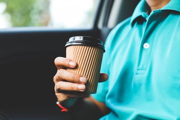 Mężczyzna z zieloną koszula trzyma filiżankę kawy w samochodzie.