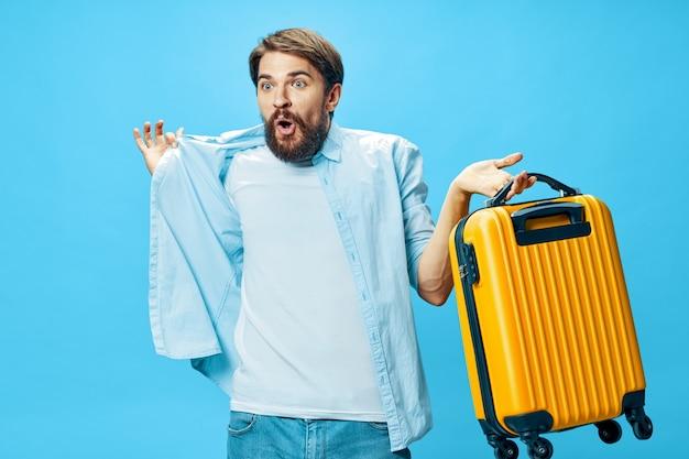 Mężczyzna z żółtą walizką na niebieskim tle podróżny model niespodzianki