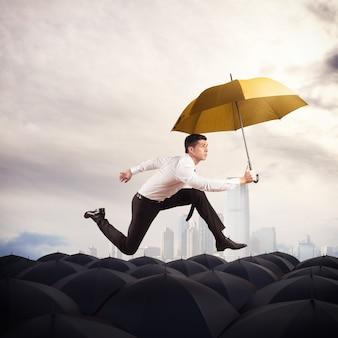 Mężczyzna z żółtym parasolem biegnie po parasolach