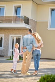 Mężczyzna z żoną i córką podziwiają nowy dom