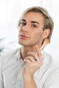 Mężczyzna za pomocą kosmetyków do makijażu