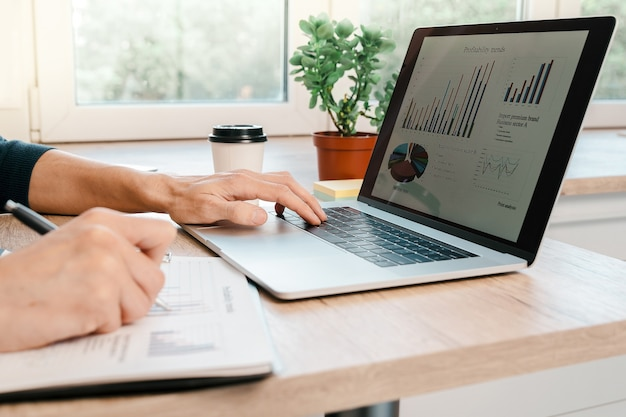 Mężczyzna za pomocą laptopa do analizy wykresów finansowych