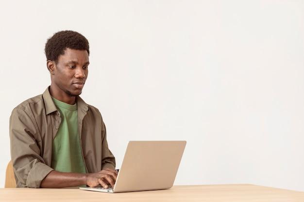 Mężczyzna za pomocą laptopa i siedząc w swoim miejscu pracy