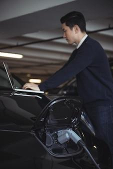 Mężczyzna za pomocą laptopa podczas ładowania samochodu elektrycznego