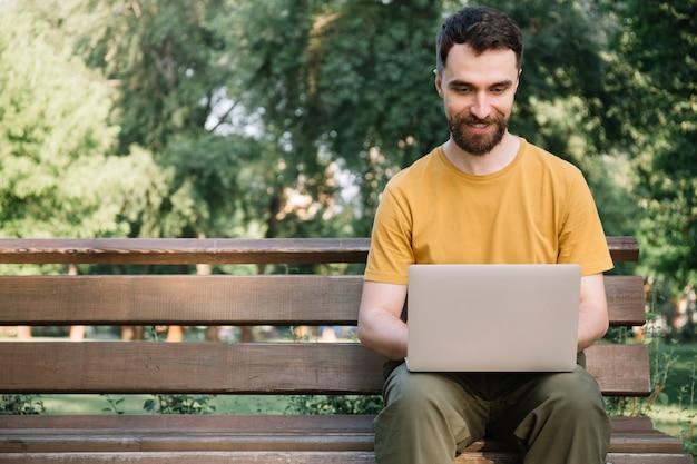 Mężczyzna za pomocą laptopa, siedząc na ławce. freelancer pracuje w parku, pisze na klawiaturze