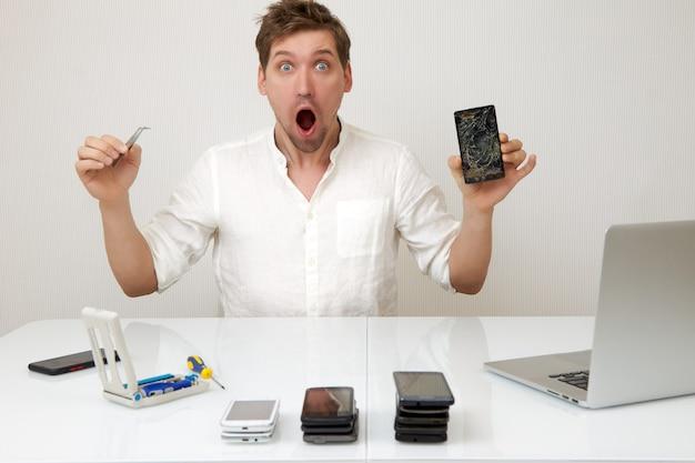 Mężczyzna za pomocą pęsety naprawi zepsuty smartfon