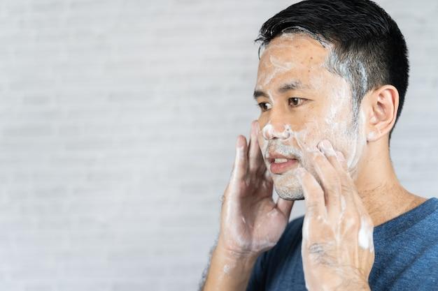 Mężczyzna za pomocą pianki myjącej twarz na szarym tle