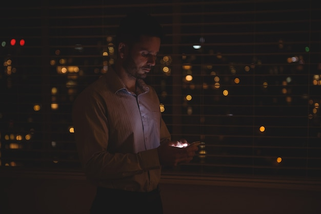 Mężczyzna za pomocą swojego telefonu komórkowego w pobliżu rolet