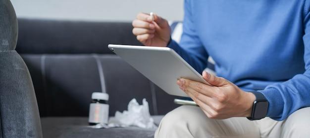 Mężczyzna za pomocą tabletu do wideokonferencji z lekarzem telemedycyny
