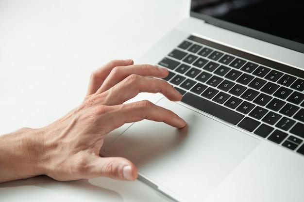 Mężczyzna za pomocą touchpada swojego laptopa