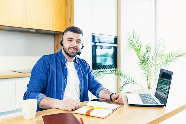 Mężczyzna za pomocą zestawu słuchawkowego z mikrofonem wykonuje rozmowę wideo online na konsultacje przy pomocy laptopa pracującego w domu