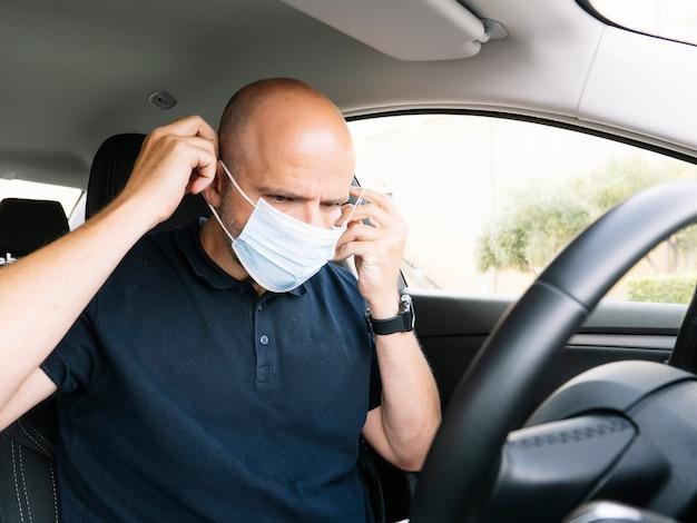 Mężczyzna zabezpiecza się maską w samochodzie