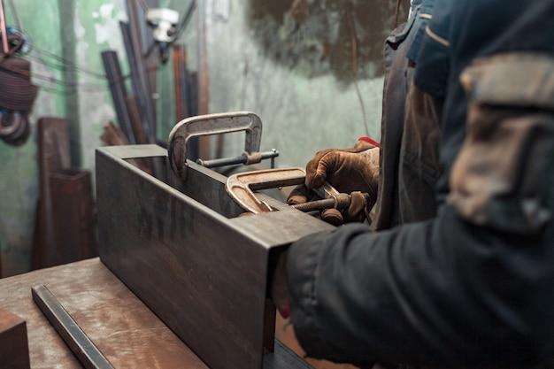 Mężczyzna zaciska produkty żelazne w zaciski c