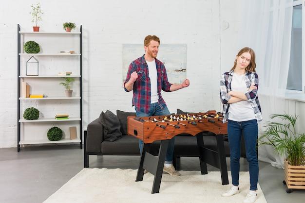 Mężczyzna zaciskając pięści z radości patrząc na smutną kobietę w nowoczesnym salonie