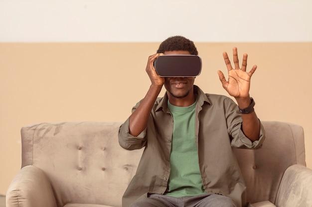 Mężczyzna zadowolony z używania zestawu słuchawkowego wirtualnej rzeczywistości