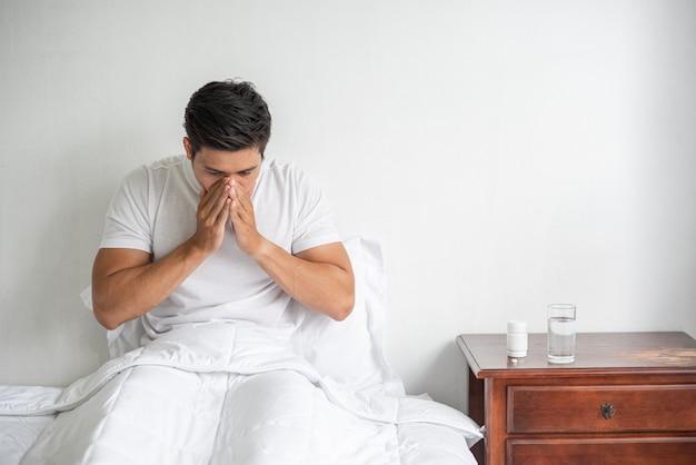 Mężczyzna zakaszlał, zakrył usta dłonią i usiadł na łóżku.