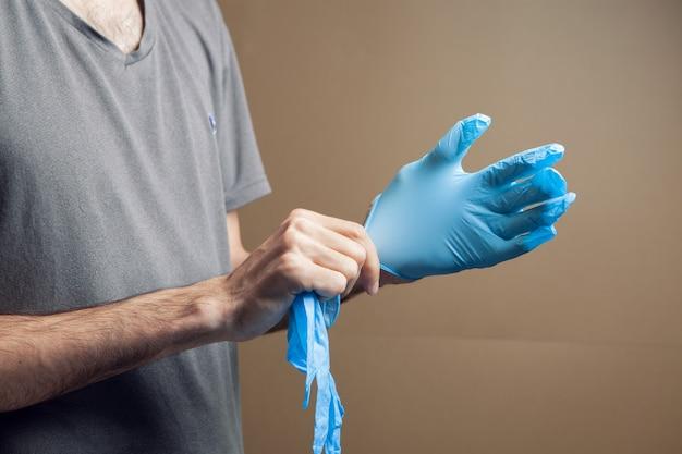 Mężczyzna zakłada gumowe rękawiczki na brązowym tle
